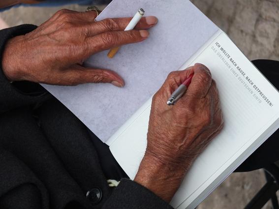 Reinhard Florian, deutscher Sinto, der mehrere NS-Konzentrationslager überlebte, beim Signieren seiner Erinnerungen am Tag der Einweihung des